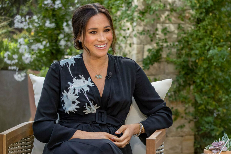 Meghan Markle, a light-skinned mixed-race pregnant woman wearing a black dress, smiles as she sits in a tan wicker chair