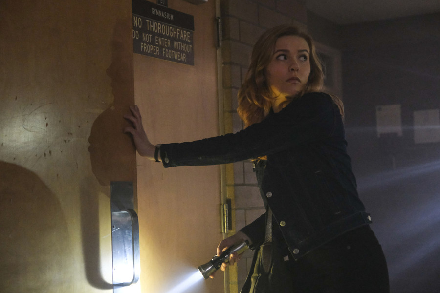 Nancy Drew, a white girl with red hair, sneaks into a room and closes the door behind her while holding a flashlight.
