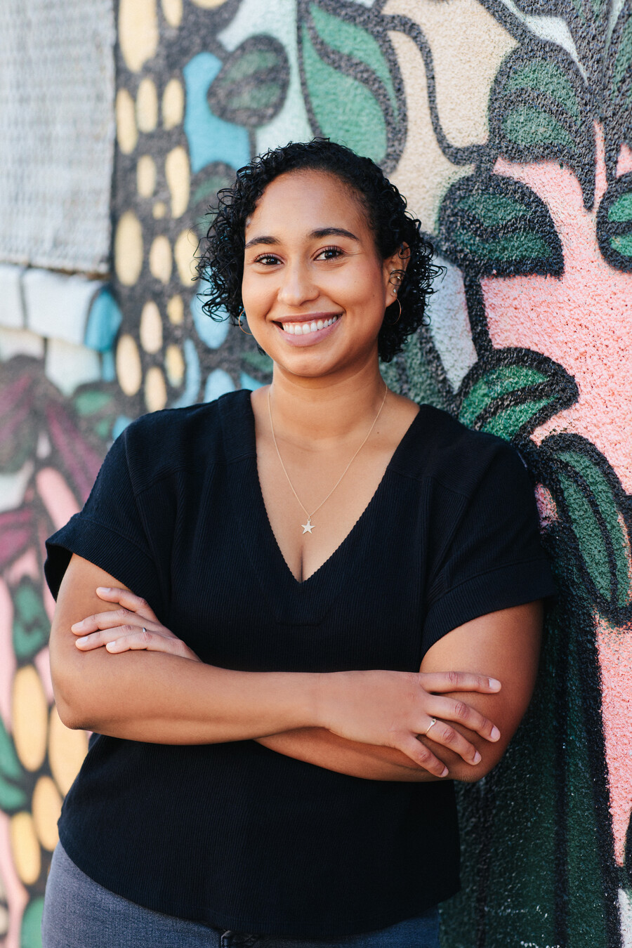 Naima Coster, a light-skinned woman with short, black hair, and wearing a black t-shirt crosses her arms and smiles as she poses against a colorful wall