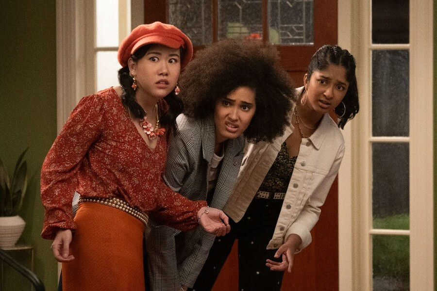 Eleanor Wong, an Asian American teenager wearing an orange outfit, Fabiola Torres, a mixed-race teenager with an afro, and Devi Vishwakumar, an Indian American teenager, stand next to each other looking appalled in Never Have I Ever