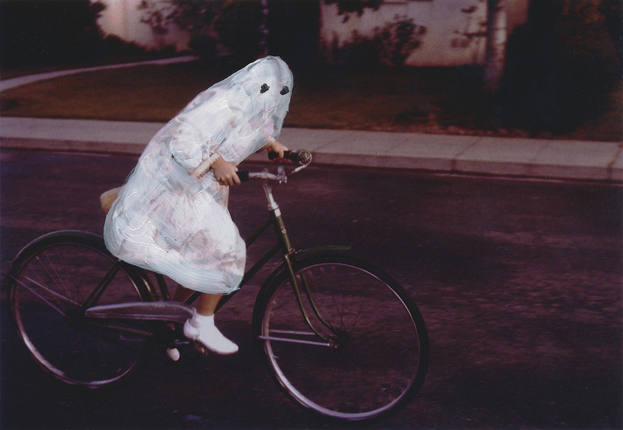 A child on a bike has a painted white sheet over them so they resemble a ghost.