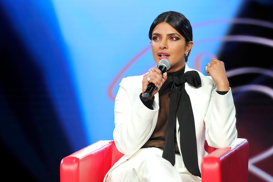 Priyanka Chopra, in white suit with black blouse, sits in red chair and speaks into microphone