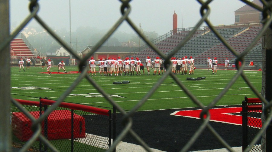 a football field with players in red seen through a chain-link fence