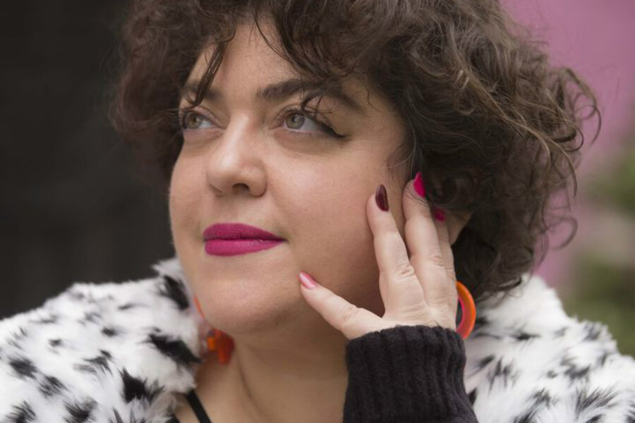 Randa Jarrar, an Arab American woman with short brown hair, holds her hand up to her face as she looks away from the camera