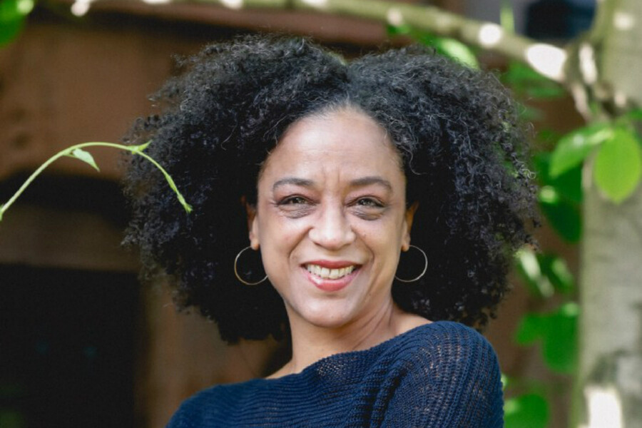 Rebecca Carroll, a light-skinned woman with a big, curly afro smiles brightly