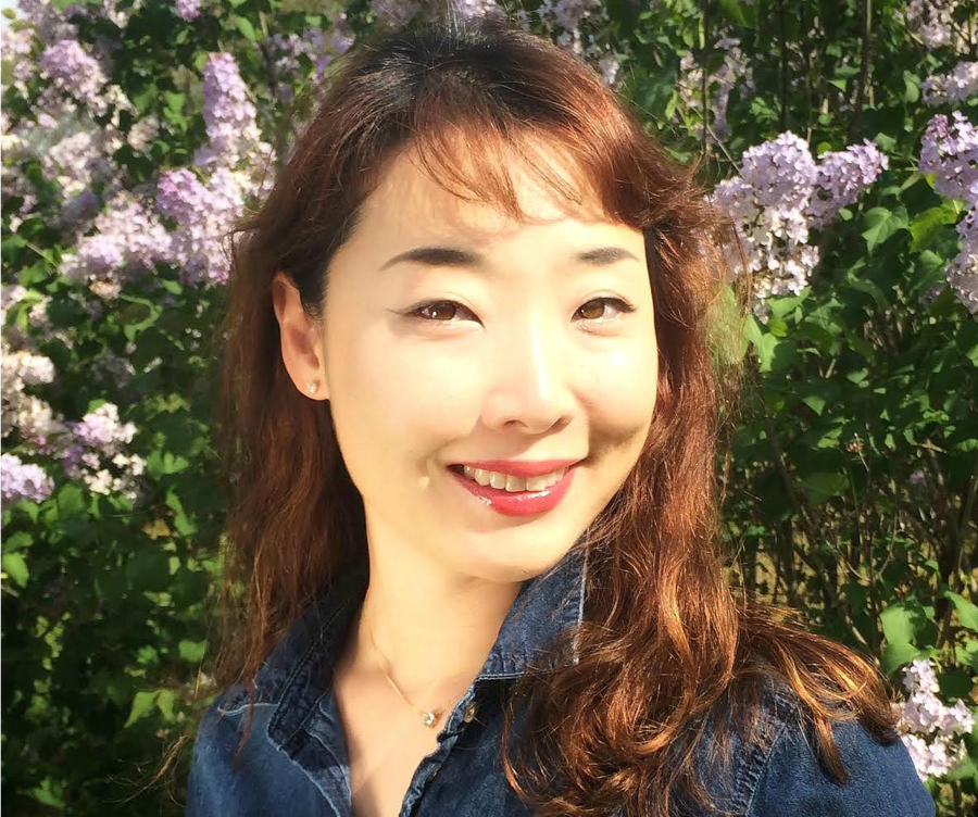 Robin Ha, a Korean author, smiles for the camera while posing in front of a wall of flowers