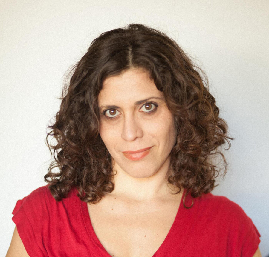 Ruby Hamad, who has wavy brown hair and large brown eyes, looks into the camera. Ruby wears a red t-shirt and stands against a neutral background.