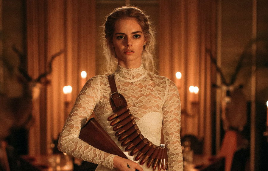Actress Samara Weaving, a white woman wearing a white bridal gown and holding a shotgun, plays Grace in Ready or Not
