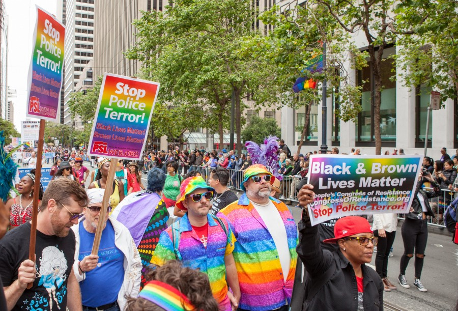 """Marchers in the Resistance contingent of the 2017 San Francisco Pride Parade hold signs reading """"Stop Police Terror"""" and """"Black & Brown Lives Matter"""""""