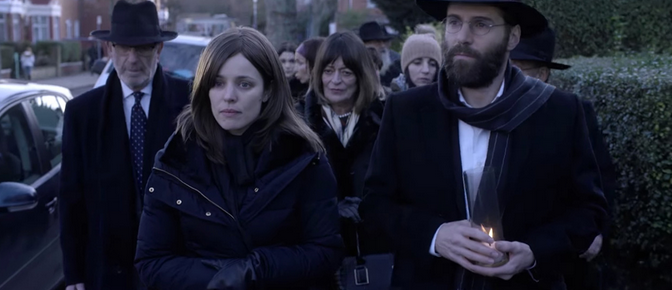 A funeral procession, dark and somber, led by Esti (Rachel McAdams) and Dovid (Alessandro Nivola)