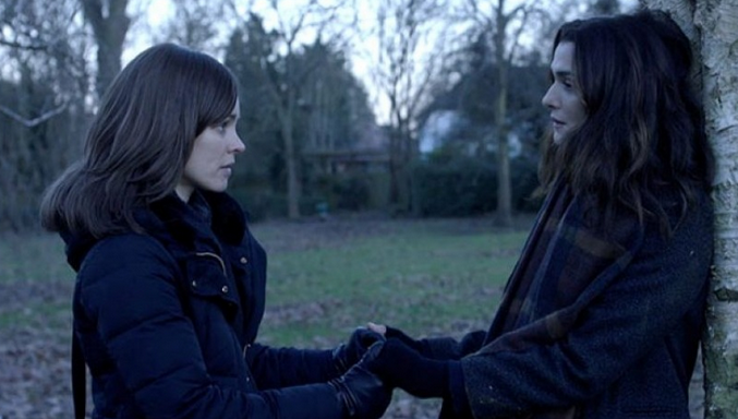 Two women (Rachel McAdams, left, and Rachel Weisz, right) face each other, hands clapsed together