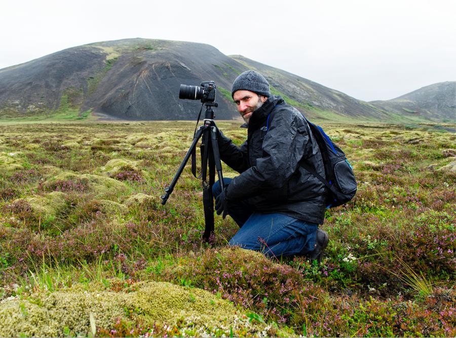 a white man kneels on a mountain while taking photos