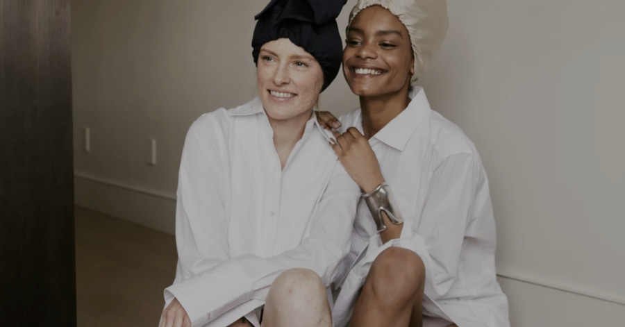 A white woman and a black woman in satin bonnets lean on each other and laugh.