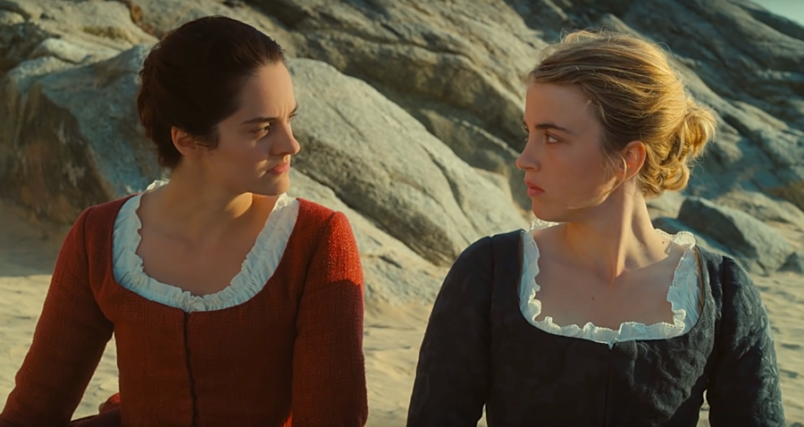 Two white women, one blond, one with dark hair, look at each other on a beach. It is 1770, and they are wearing frilly dresses and have their hair back in wavy buns.