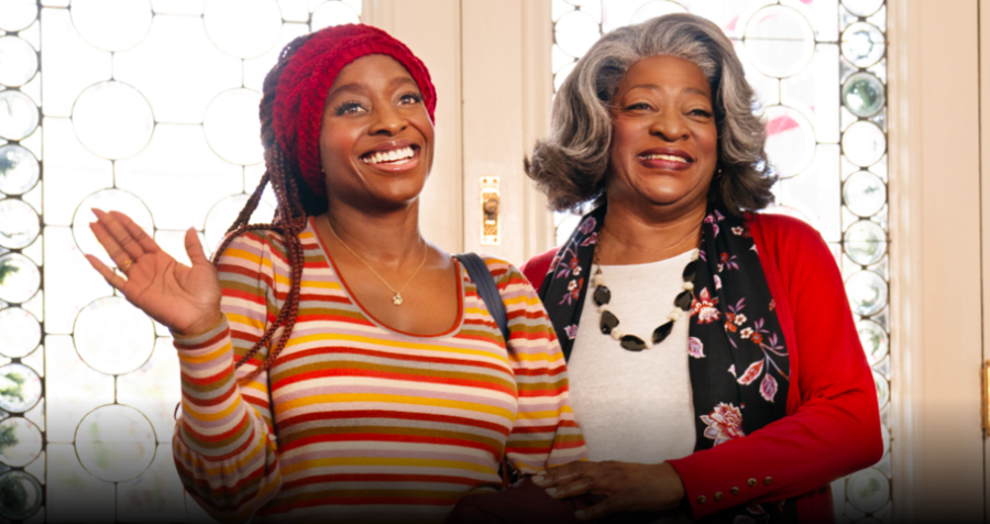 One young Black woman and a Black woman with gray hair stand smiling in a doorway while wearing winter clothes.