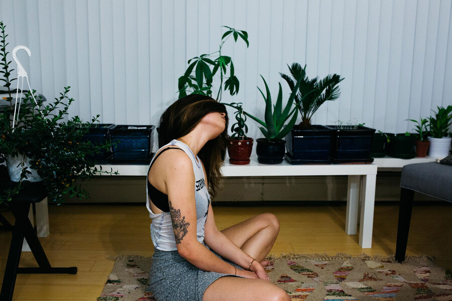 a thin, white woman sits on the floor in a meditation pose with hair wrapped around her eyes