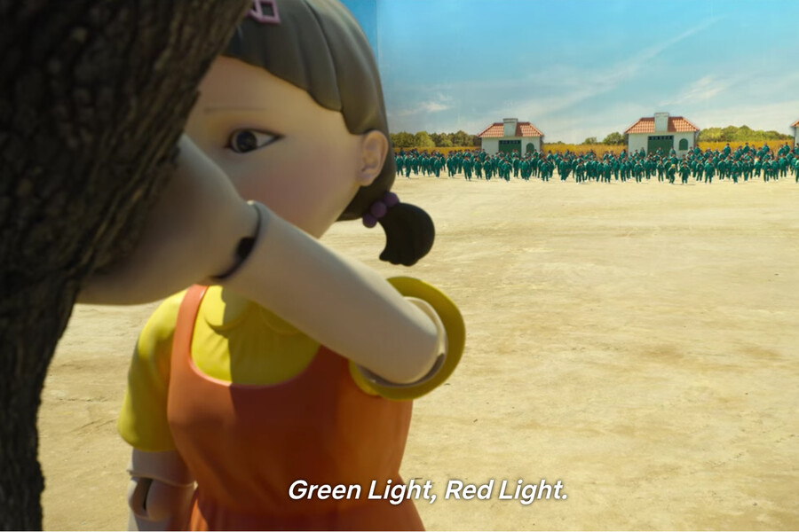 """A huge animatronic girl has its back turned against a tree with hundreds of people in green jumpsuits lined up in the distance behind her. The subtitle onscreen reads """"Green Light, Red Light"""""""
