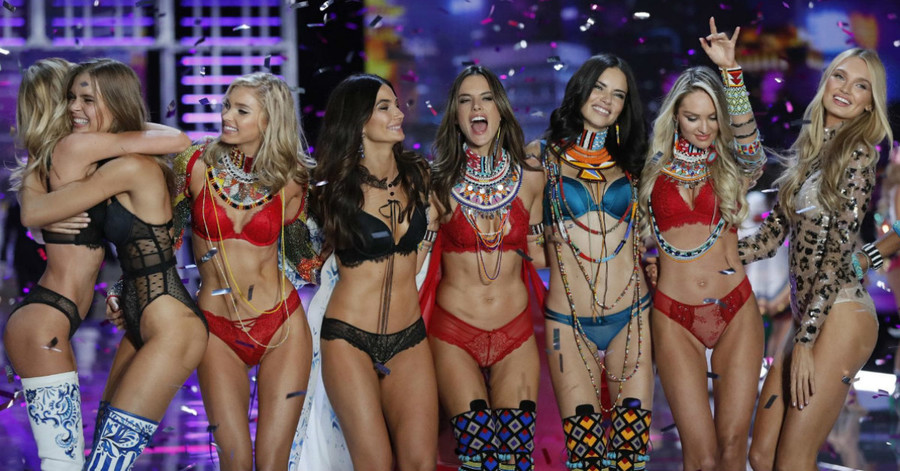 eight thin, white models embracing and celebrating after a runway show