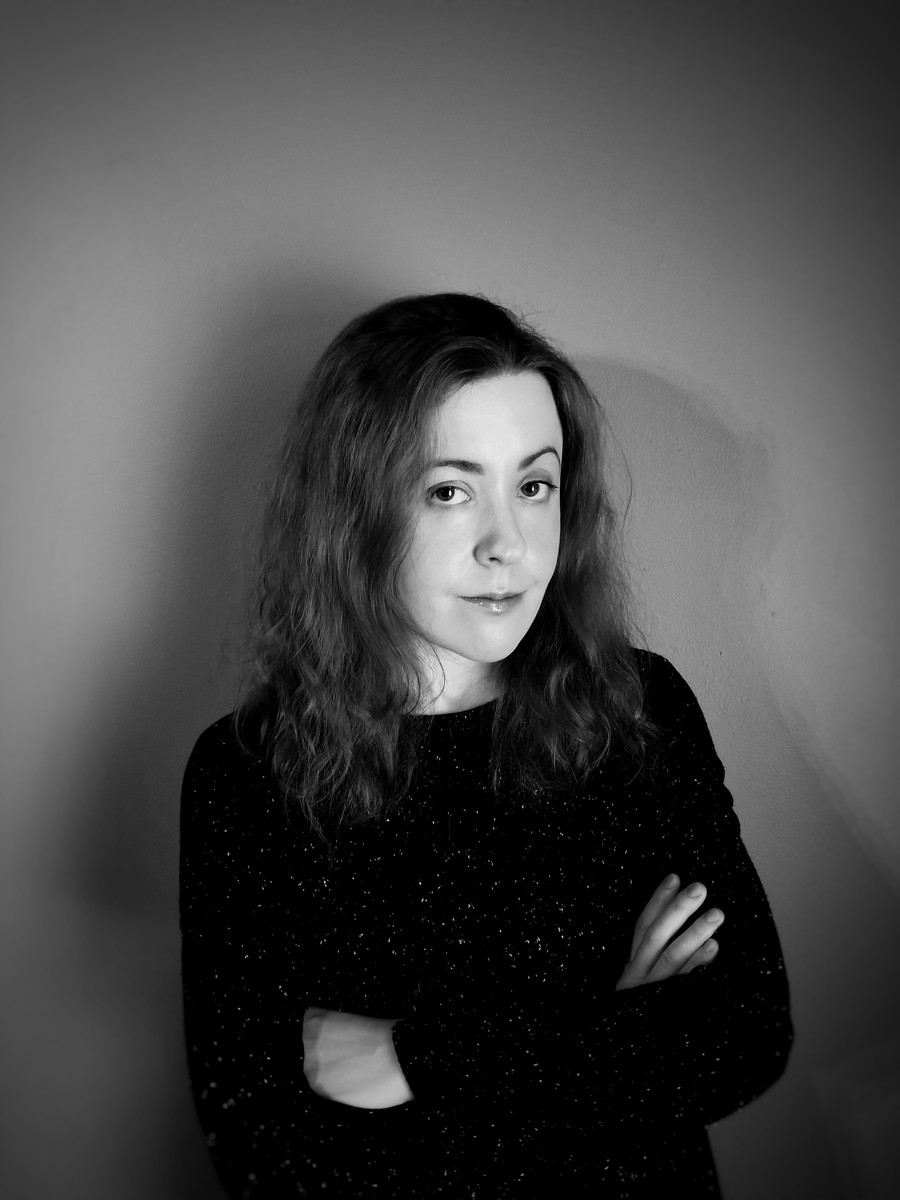 black and white photo of white woman with brown hair and a black shirt staring at the camera