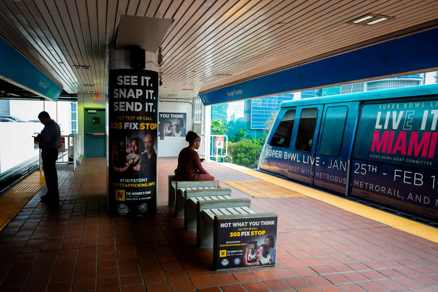 a Black woman sits at a train station watching a train with an advertisement
