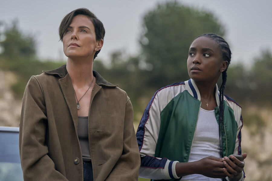 """Nile, a young Black woman with braids, and Andy, a white woman with short dark hair, lean on a car in """"The Old Guard."""""""