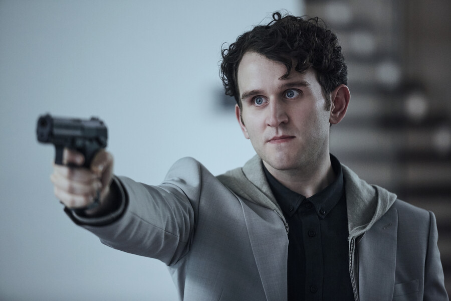 Harry Melling as Merrick, a white man in a trench coat with dark hair. He holds a gun.