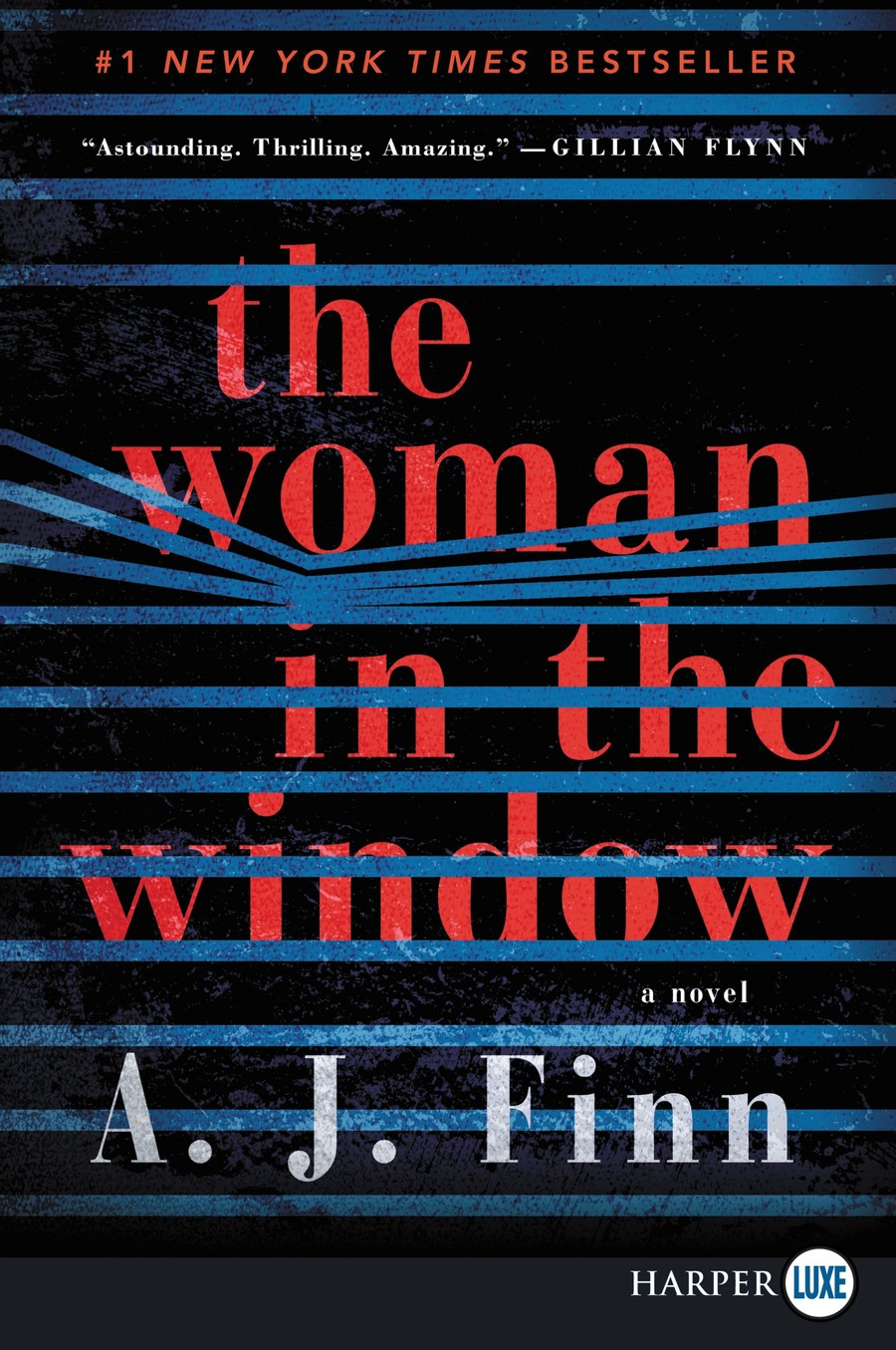 The cover of The Woman in the Window by A.J. Finn shows the text peeking through window blinds