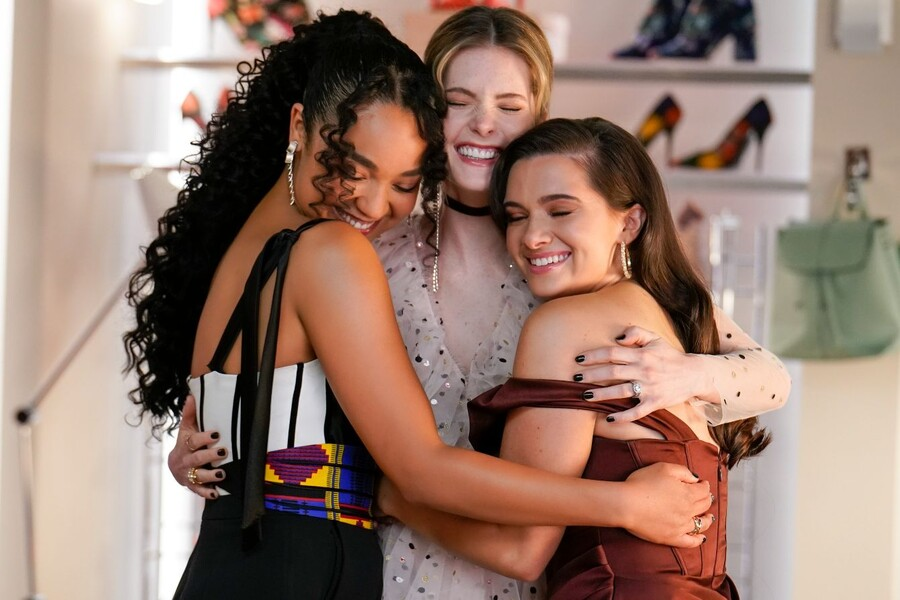 A photo of actors Aisha Dee, a biracial woman with curly black hair, Meghann Fahy, a white woman with light brown hair, and Katie Stevens, a white woman with long, dark brown hair, are hugging on the set of their show The Bold Type.