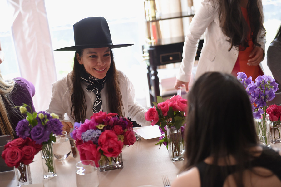 Thinx Co-founder Miki Agrawal, a woman wearing a large hat and a scarf around her neck, sits at a table with flowers on it.