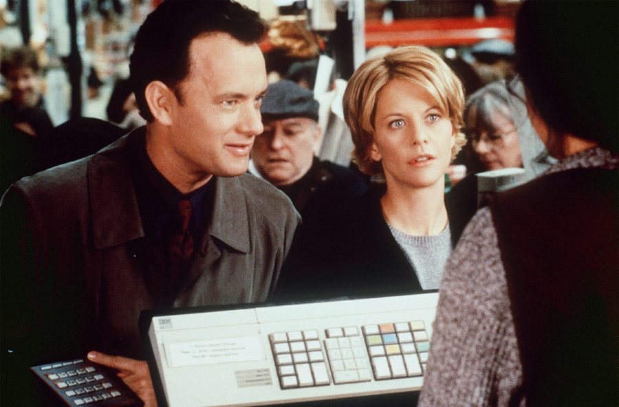 a white man with brown hair stands next to a white woman with short, blonde hair looking at a store clerk
