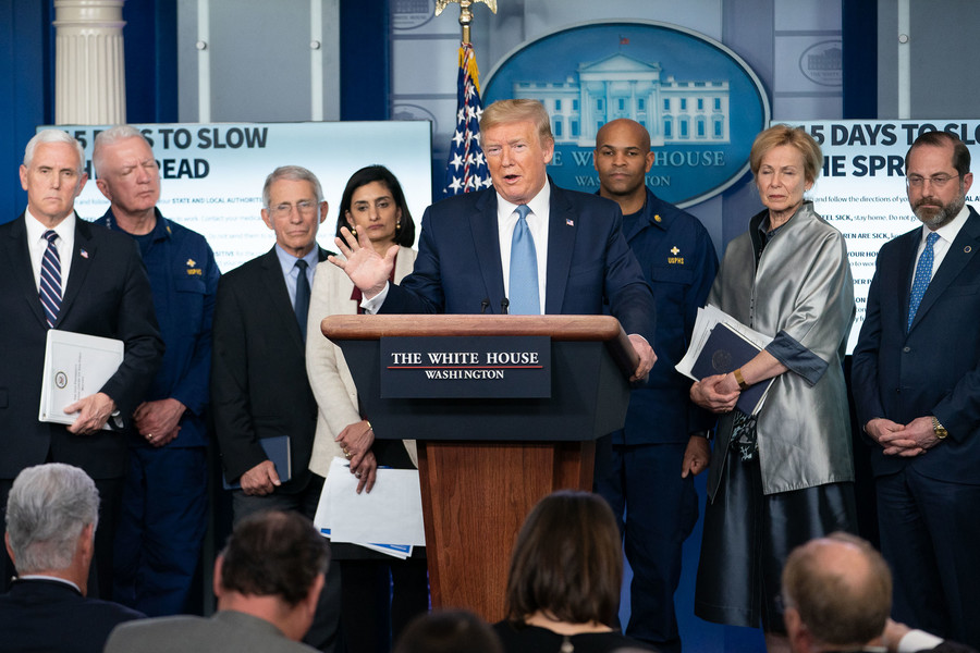 Donald Trump, a white dumpy man, stands behind a podium while seven people stand behind him