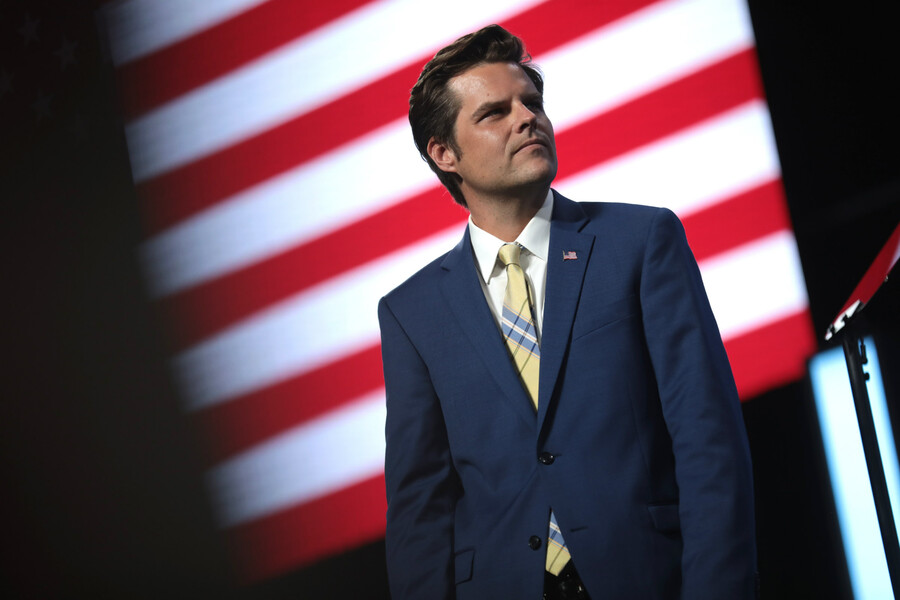 Congressman Matt Gaetz, a white, thin man with brown, short, wears a blue suit and yellow tie posing in front of an American flag