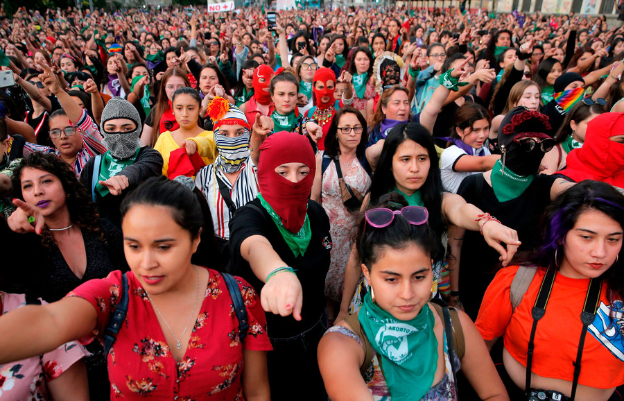 a group of Chilean women protestors all point in a single direction during a rally