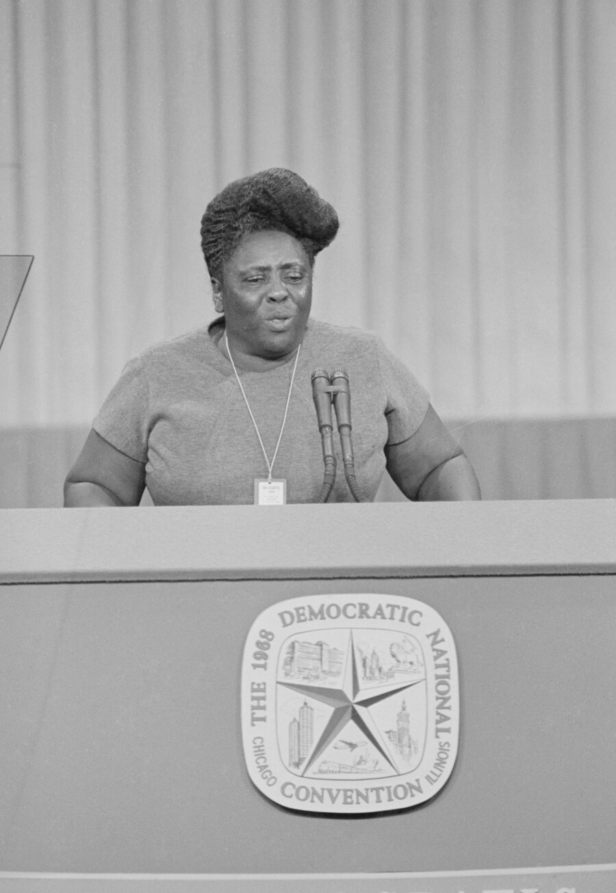 A black and white image of activist Fannie Lou Hamer, a Black woman, speaking at a podium with a logo for the 1968 Democratic National Convention.
