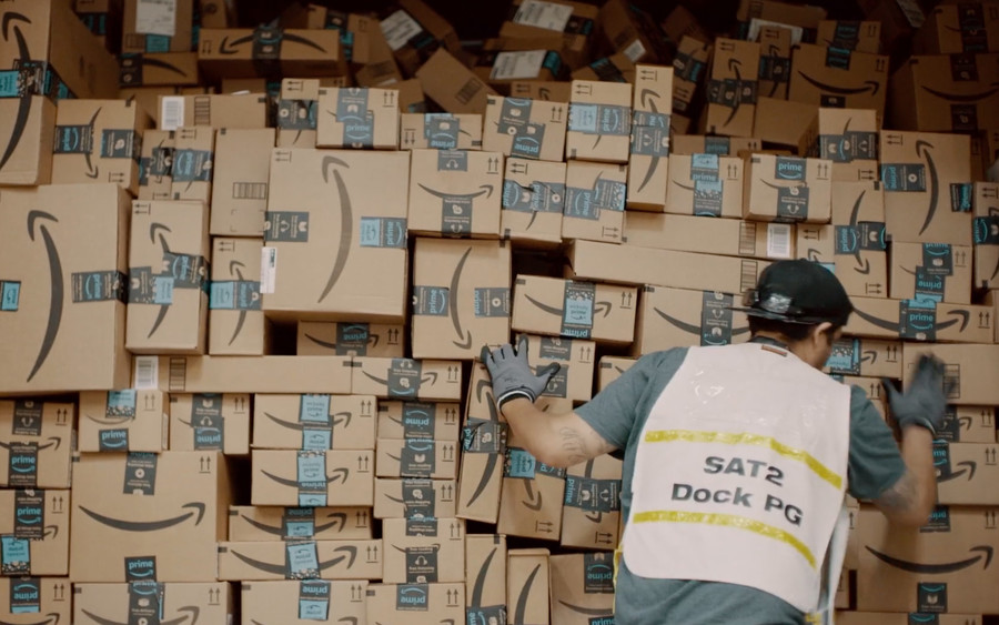 Person in a green shirt, wearing gloves and packing Amazon shipping boxes.