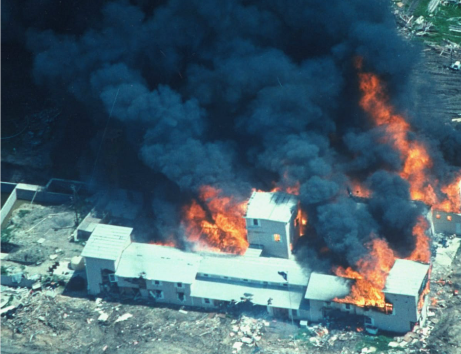 an aerial view of a white compound in Waco, Texas, engulfed in flames in 1993