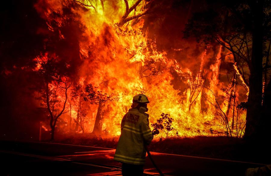 image of an Australian fire fighter in front of a huge blaze of fire