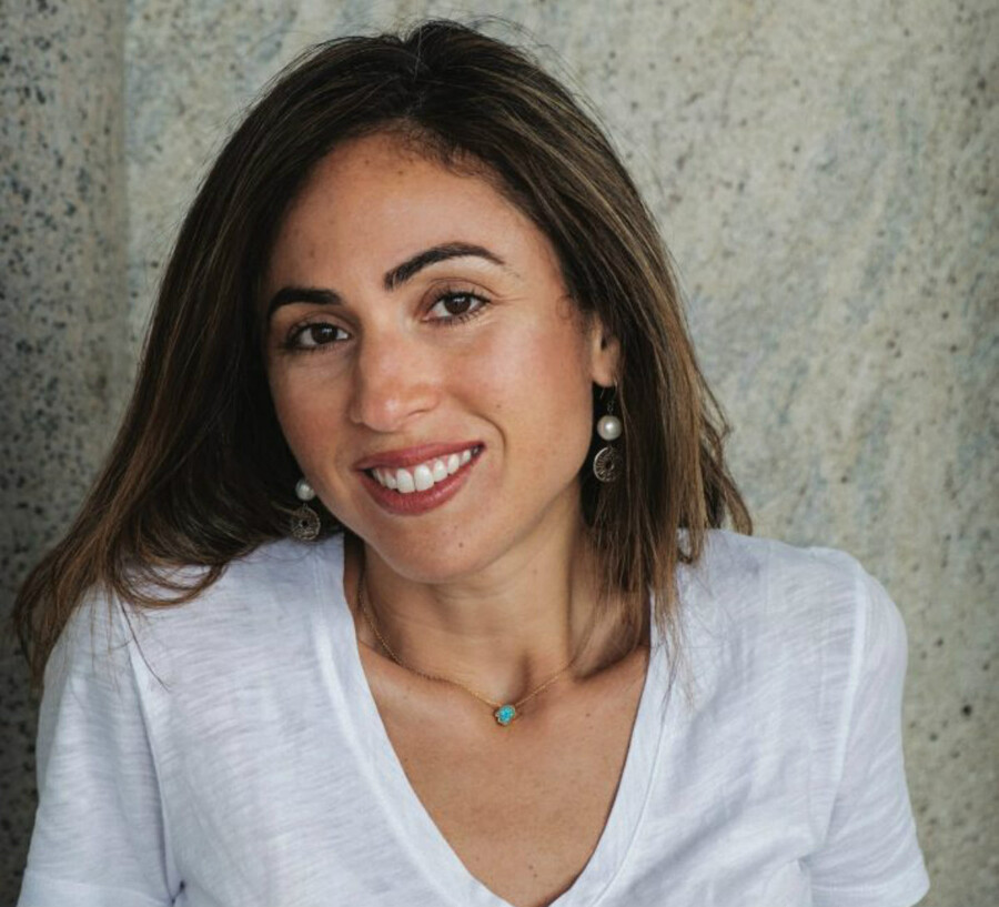 Zaira Arafat, a Palestinian American writer with shoulder-length brown hair, sits in front of a concrete wall and smiles