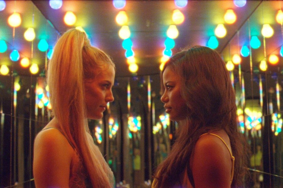 Riley Keough as Stefani, a thin, white woman with a blond ponytail, looks at Taylour Paige as Zola, a thin Black woman with long, brown hair in Zola