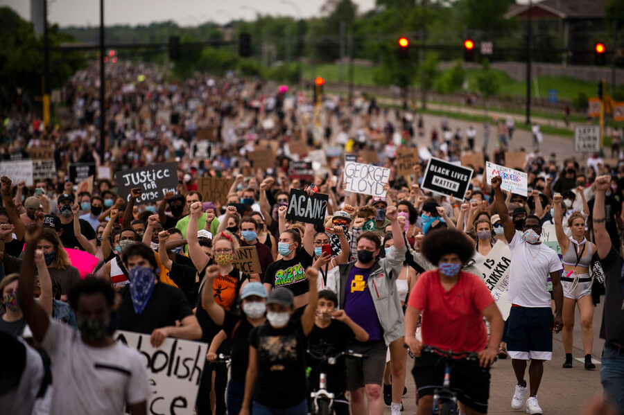 protestors, some walking and some on bikes, march with signs through the street to protest the murder of George Floyd