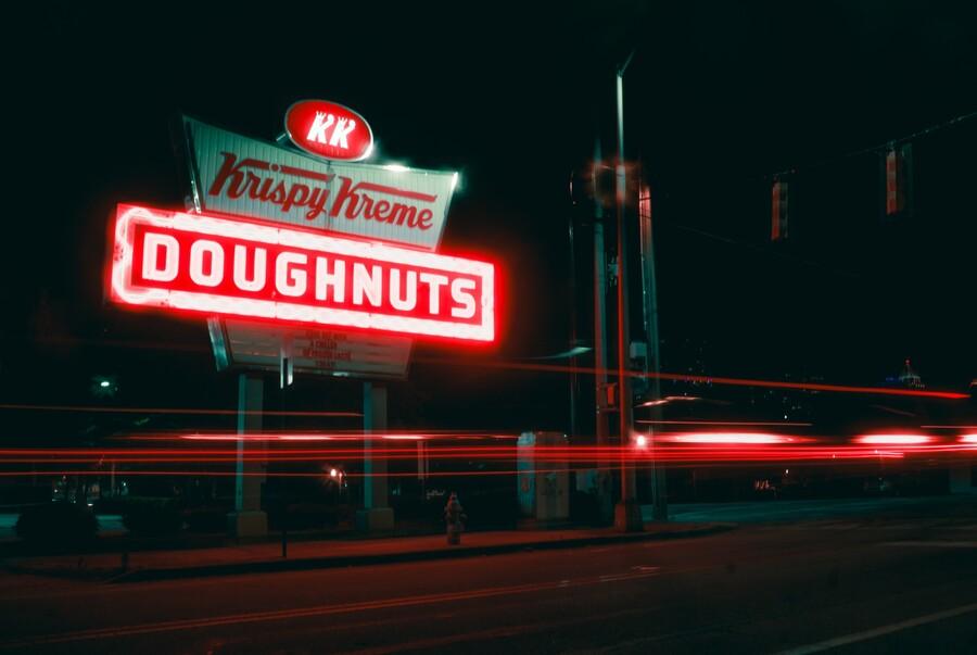 A Krispy Kreme sign glows on a street.