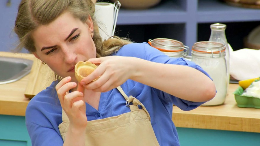 A white woman is staring intently at a pastry shell as she shapes it into a cup.