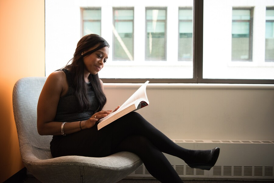 A Black woman sits on a bench and reads a book. Her hair is in long braids, she's wearing a dress, and she's smiling.
