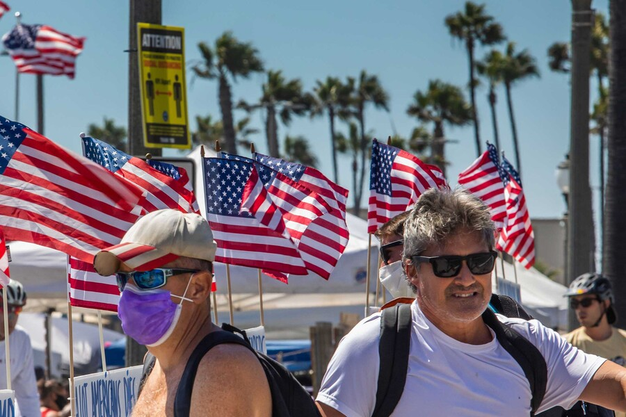 two white men sit on a boardwalk in California, in front of a row of U.S. flags, without masks on