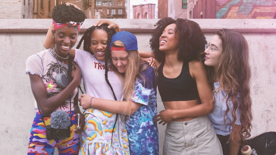 A diverse group of young women hug and lean on each other.