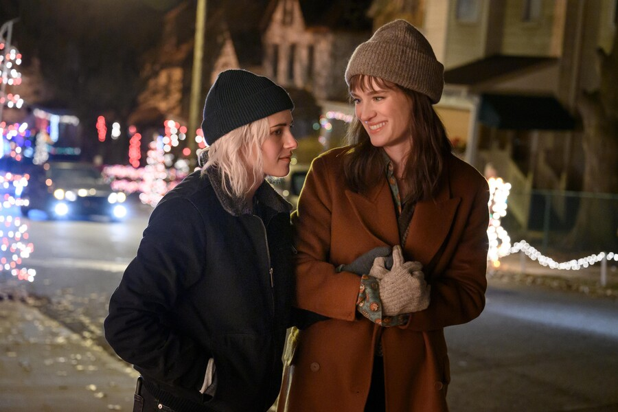 Two white women lean into each other and laugh in a movie theater. One has short blond hair and the other has brown hair with bangs. They are wearing winter clothes.