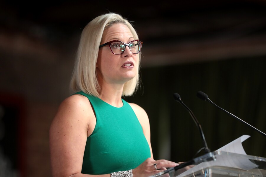 U.S. Senator Kyrsten Sinema, who is white with blond hair and glasses, speaking with attendees