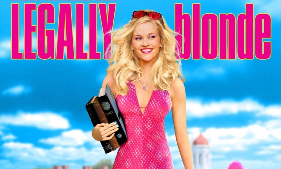 Reese Witherspoon as Elle Woods, a white woman with long blond hair who wears a pink dress and smiles.