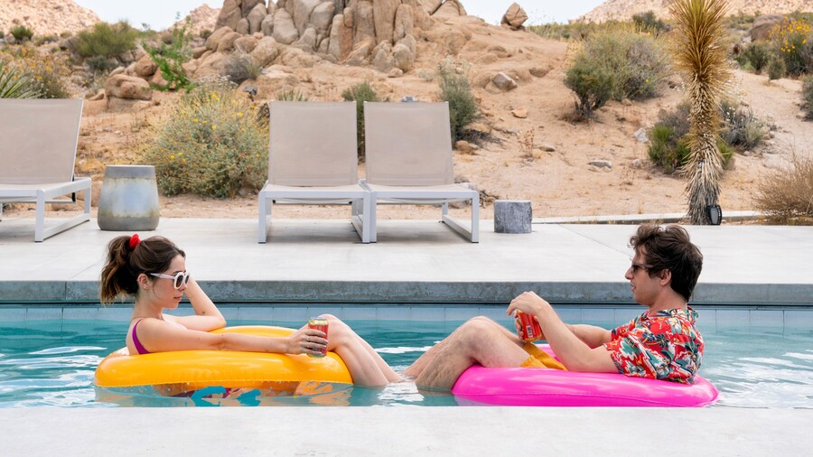 Two white people wearing sunglasses relax on floats in a pool, the desert behind them.