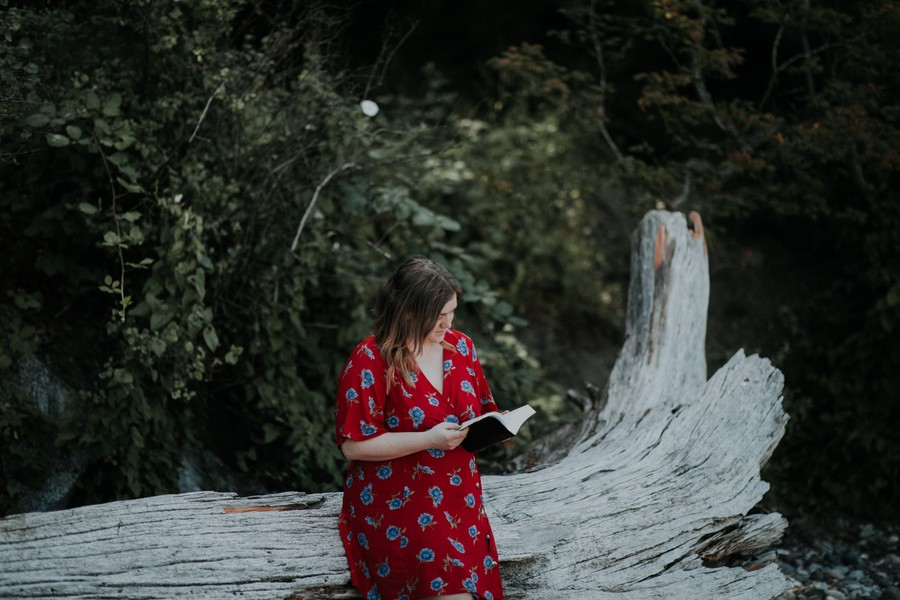 a white woman sits outside on a log reading a book